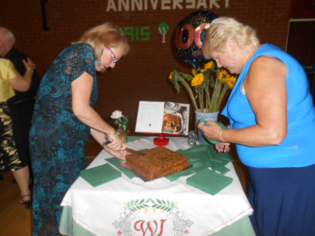 Chris Smith & Jan Middleton cutting the cake at the 100 year celebration meal